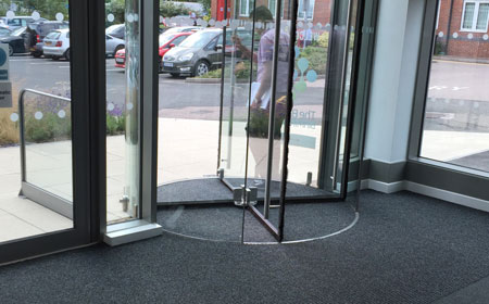 Hospital entrance with revolving door mat